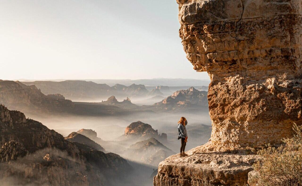 girl-standing-on-brown-rock-formation